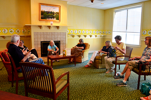 A group of people gather to discuss a book in the reading room for the Hygge Reading Party at the Robins Library