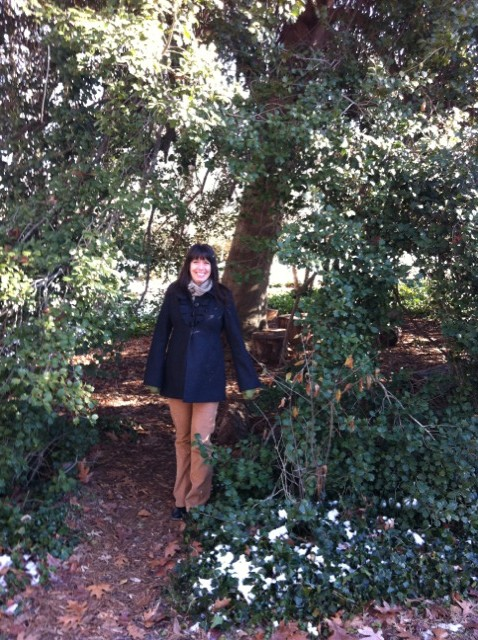 """Kristin Mullen at the entrance to the famous """"secret"""" holly tree."""