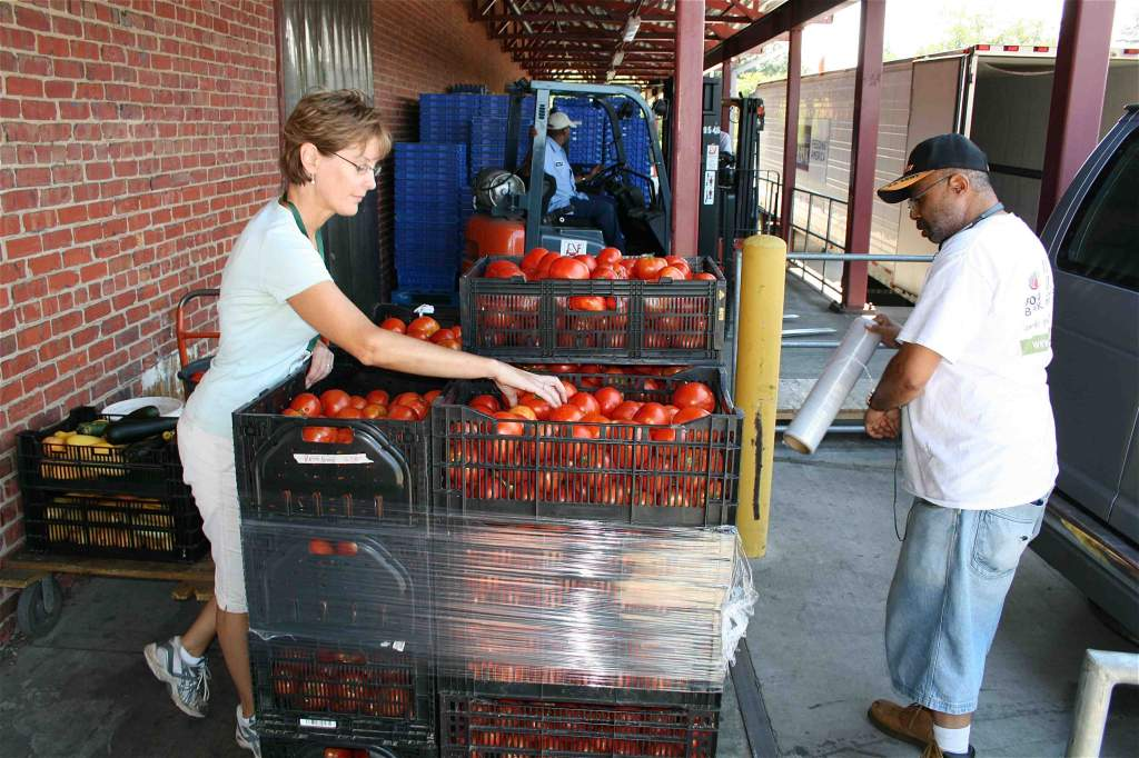 Lisa organizes the tomato crate contents to facilitate stacking, while FeedMore employee Ralph secures the stack.