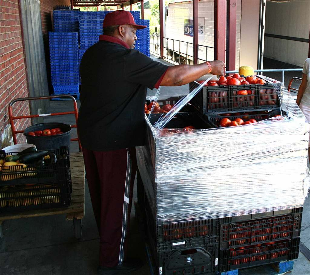 Paul Adams - Community Kitchen Food Resource Assistant - helps to secure the load to prevent the stack from toppling over.