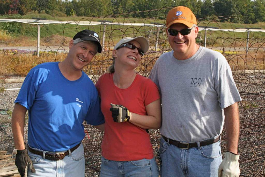 Kevin, Christa and George take a break from pulling tomato stakes & vines. I don't know what it is about hard labor that makes the CKG volunteers laugh so much. I hope it's not simply the sight of the photographer wearing shorts.