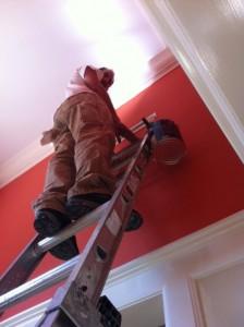 New colors! A workman painting brilliant red & crisp white trim.