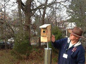 Buz Sawyer inspecting a bluebird house.