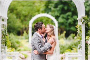 A kiss under the arbor in the Grace Arents Garden at Sarah and Simon's Lewis Ginter Botanical Garden Wedding. Photos by Steven and Lily photography