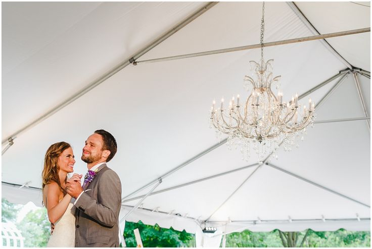 A chandelier hanging under the tent, for a classy touch. Photo by Steven and Lily photography.