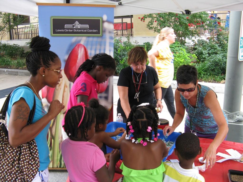 "Children's Garden volunteers ""digging in"" with the summer reading participants."