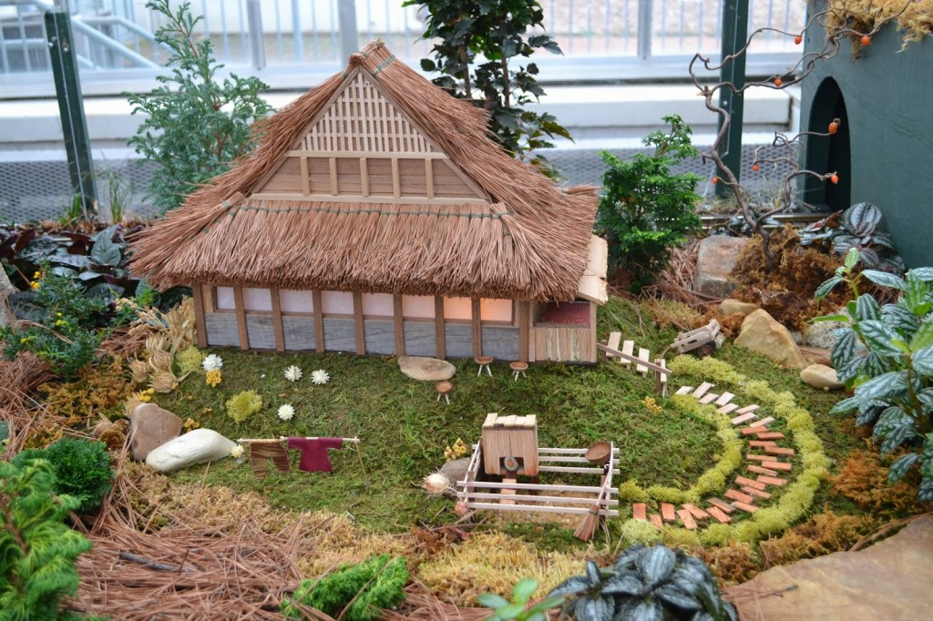 Asian-style house from the 2012 display.  Pine needle thatched roof and colorful pressed leaves look like clothing drying on the clothes line.
