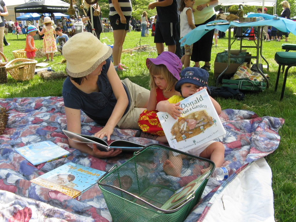 a family enjoying a few books in the shady reading spot.