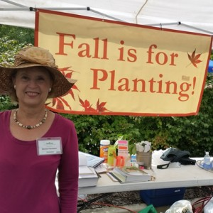 Fall Plant Sale volunteer with Fall is for Planting sign