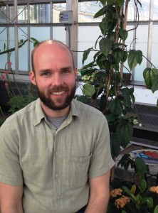 Butterfly Curator Matthew Daniel sitting in the conservatory next to a plant bed