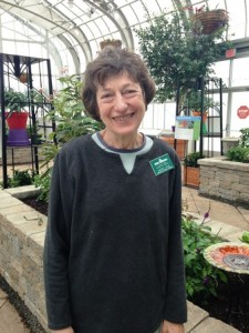 Butterfly Curator Sherry Giese standing in the conservatory next to stone plant bed