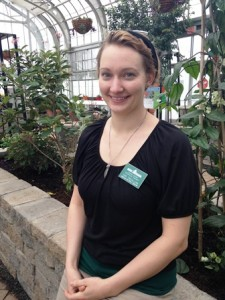 Butterfly Curator Tori Trevillian sitting in the conservatory next to stone plant bed