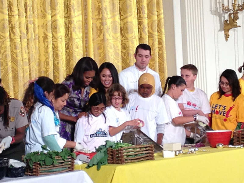 The First Lady looks on as Lilah and Amina grate kohlrabi
