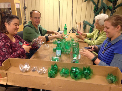 Staff and volunteers making flowers out of recycled bottles.