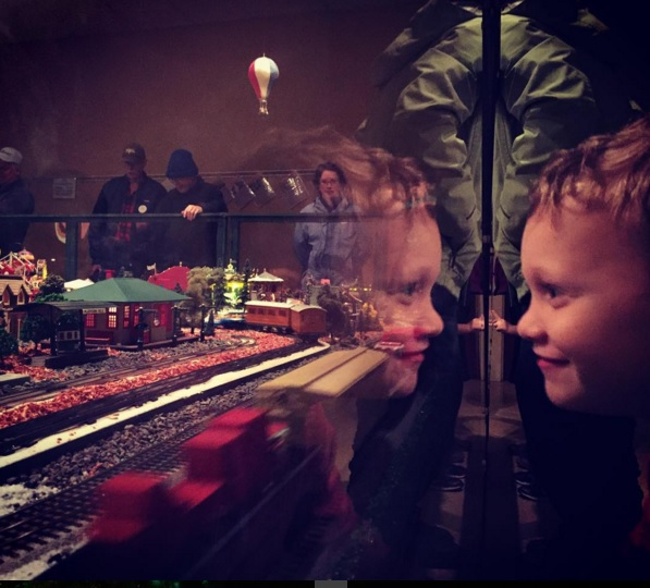 Boy looking at trains with reflection