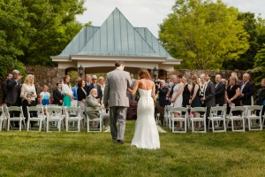 Bride walks down the isle at an outdoor wedding. Image by Katelyn James Photography