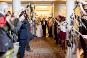 A newly married couple exits the Robins Visitor Center through a tunnel of streamers. Image by Mary Otanez Photography.