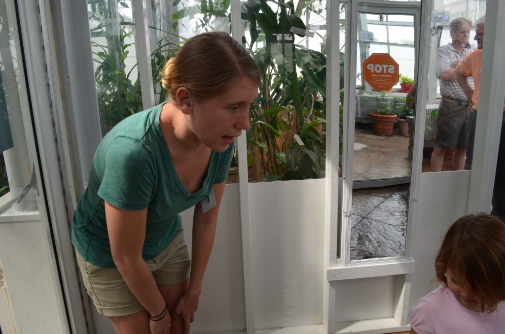 Kelsey Deans giving two little girls instructions before entering the Butterflies LIVE! exhibit.