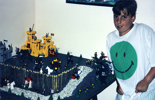 "A vintage photograph shows young Brian Korte with a LEGO® set and an elaborate world with a yellow castle and ""Forestmen"" he created with the bricks."