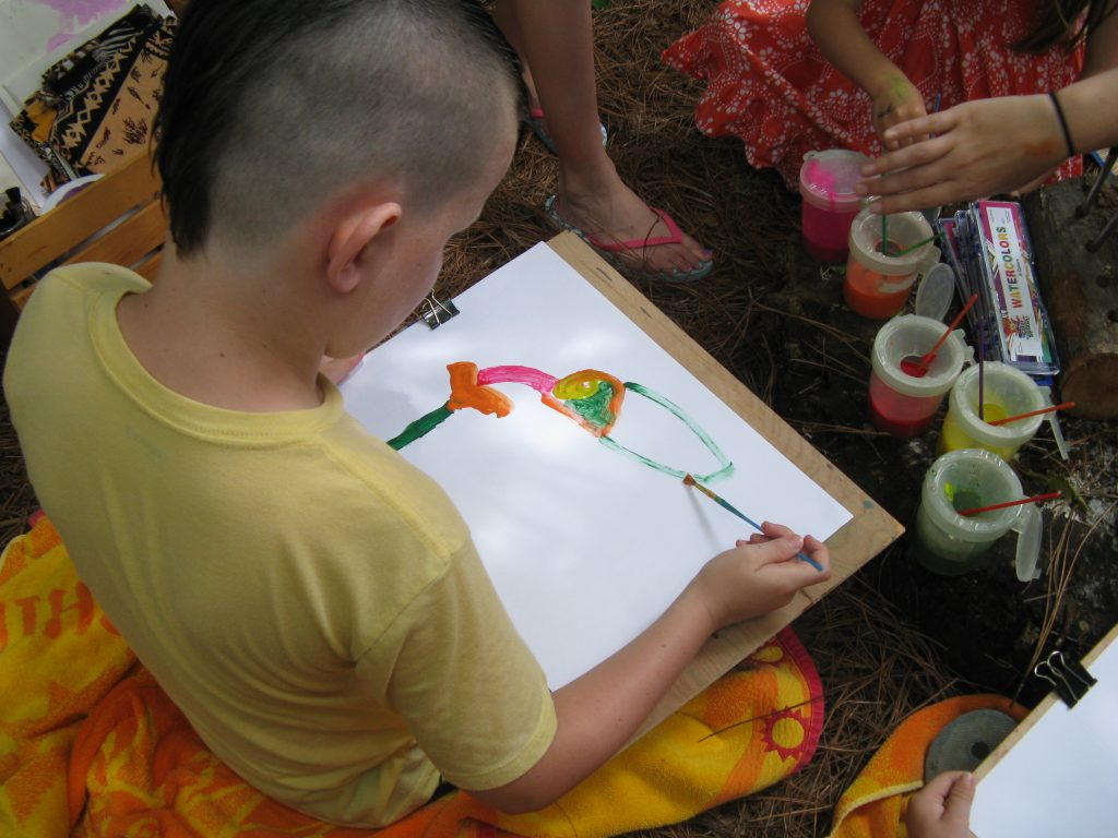 Gabriel started by painting the orange flower and then moved onto the hummingbird, starting with its beak, head and body.