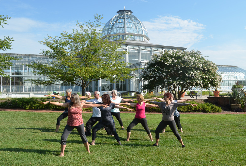 Warrior Pose yoga class in the rose garden