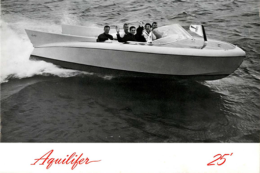 Six people ride on a light colored boat in a black and white photograph. The people are smiling and waving.