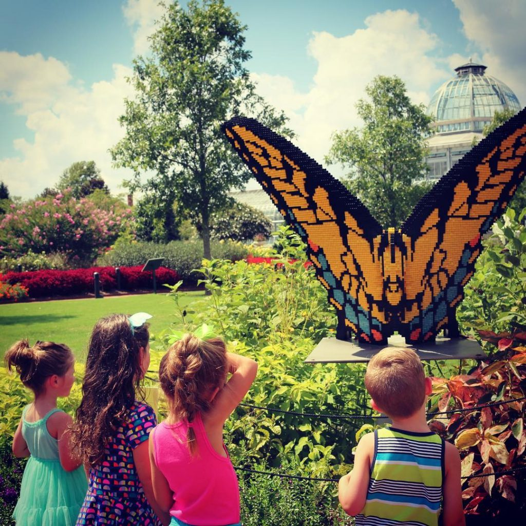 Kids enjoying the Eastern Swallowtail Butterfly LEGO brick sculpture from Nature Connects: Art with LEGO Bricks. Photo by @carollane1111