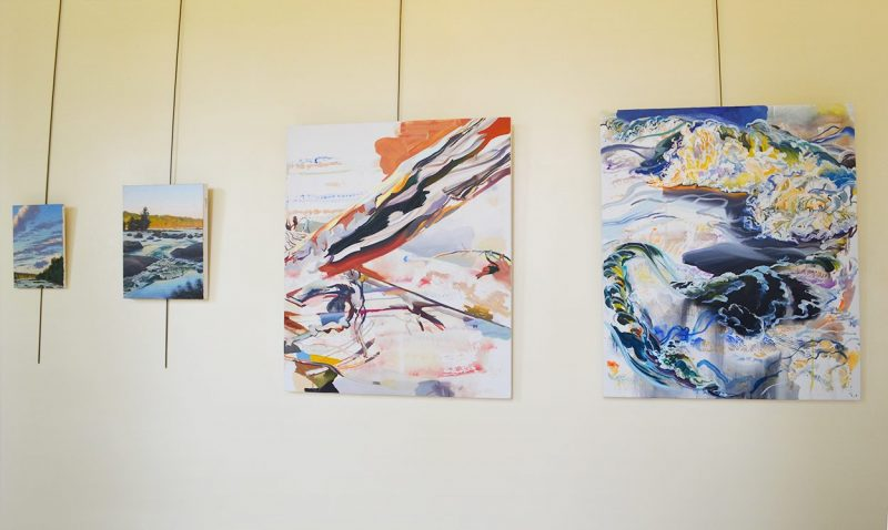 Four paintings on the wall depict the James River. Two are realisitic paintings, while two are abstract. One has red tones and the other has blue tones.