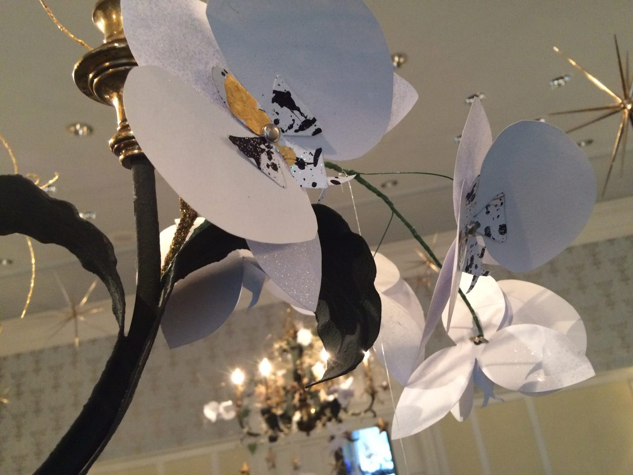 Paper orchids handmade by Colten Blackburn and Garden volunteers. A trio of sepal petals cut from opalescent paper and Blackburn's template forms the base of each bloom. Side petals are cut out of heavy ivory paper. In the center, the flower's anther cap and stigma were fashioned from of the same ivory paper, spattered with metallic gold and purple acrylic. Based on orchids in the Garden's collection, the elegant blooms mimic moonlight in the evening.