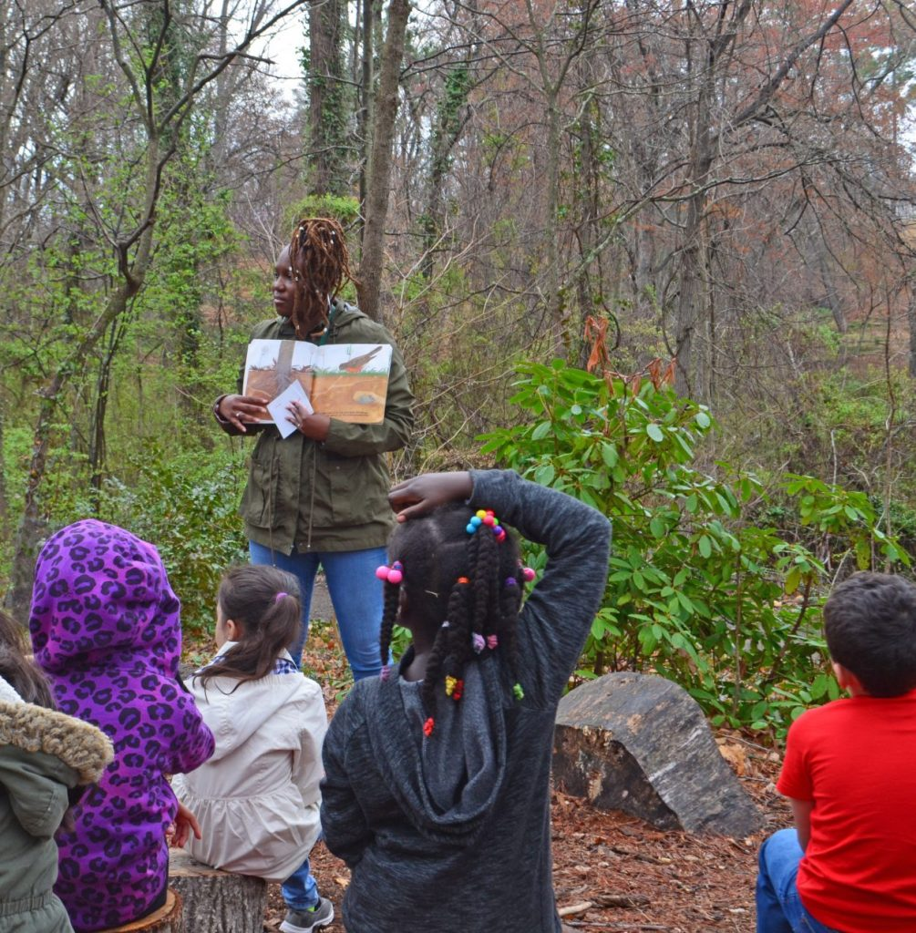 "Tarneshia Evans reading a story to a field trip class at the ""amphitheater"" along the Tree Trail in the Children's Garden."