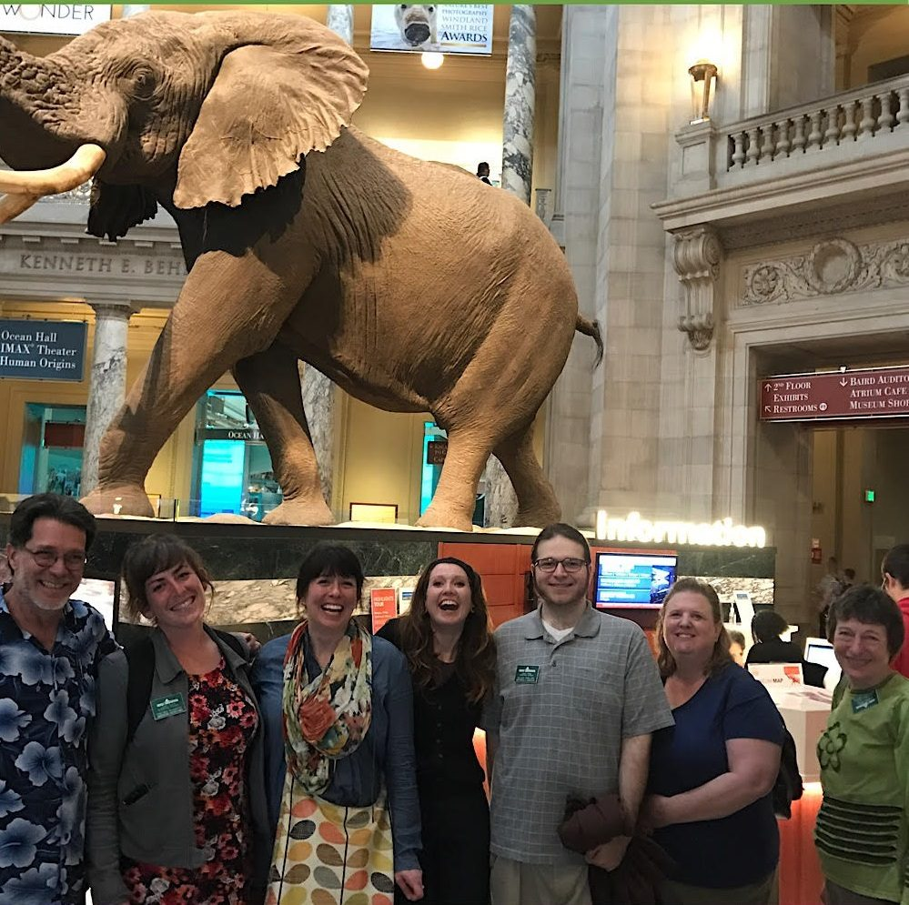 Curators with Conservatory Horticulturist and Exhibition Manager stand in the main entrance of the National Museum of Natural History with the Smithsonian elephant behind them.