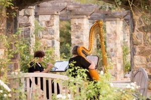 Acoustic instruments play at outdoor wedding venue, the Rose Garden. Image by J&D Photography
