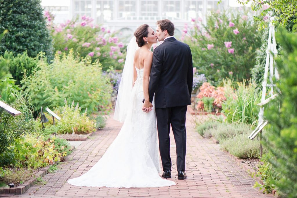 Couple kisses at their outdoor wedding at Lewis Ginter Botanical Garden. Image by Karin Nichole Photography.