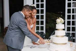 Cutting wedding cake at outdoor wedding at Bloemendaal House. Image by David Abel Photography.