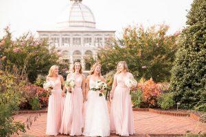 Bridesmaids walk through the Central Garden during an outdoor wedding. Image by J&D Photography.