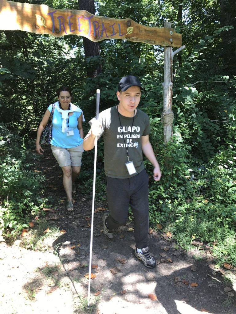 """David Palma-Caria, who has a vision impairment, walking with his translator Roxana Wolburg out of the """"Tree Trail."""""""