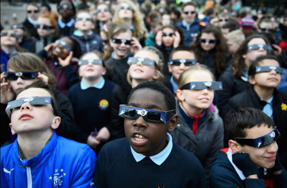 Children watching the solar eclipse wearing protective shades. Image by Mark Margolis.