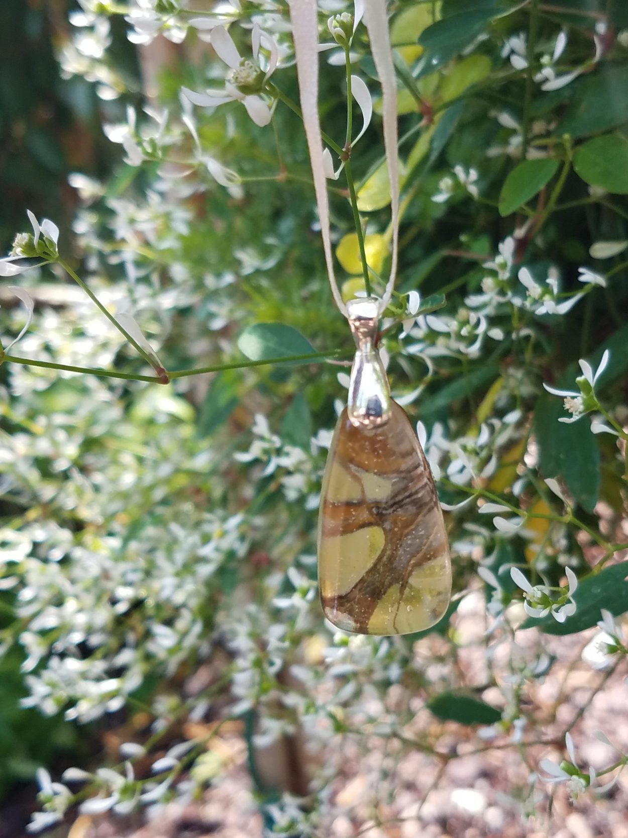 Paper Kite Butterfly wing pendant held against small white flowers