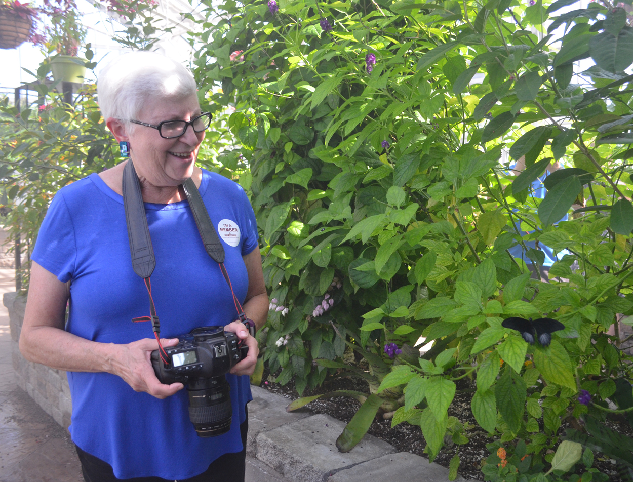 photo of photographer Jeanne Schlesinger smiling next to a butterfly
