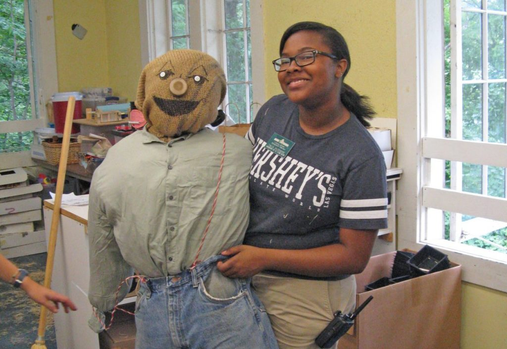 intern Lia Bazemore with her scarecrow