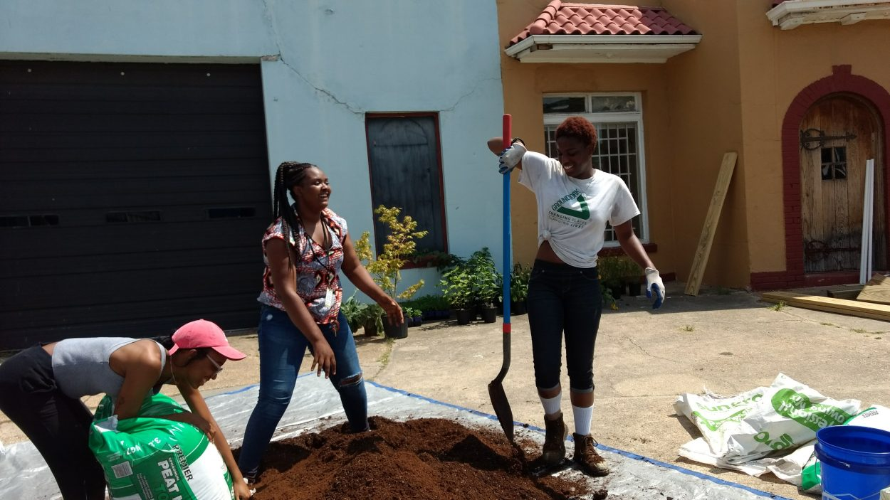 A student tried to balance her spade while others stood by and laughed in support.