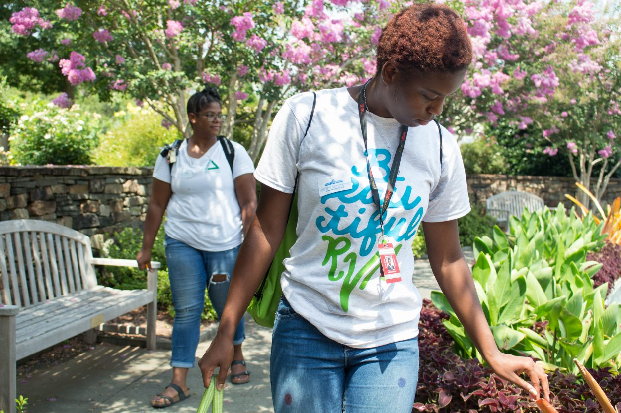 A black student wearing a Beautiful RVA white shirt. She was rubbing her fingers against a leaf as she walked past the Central Garden.