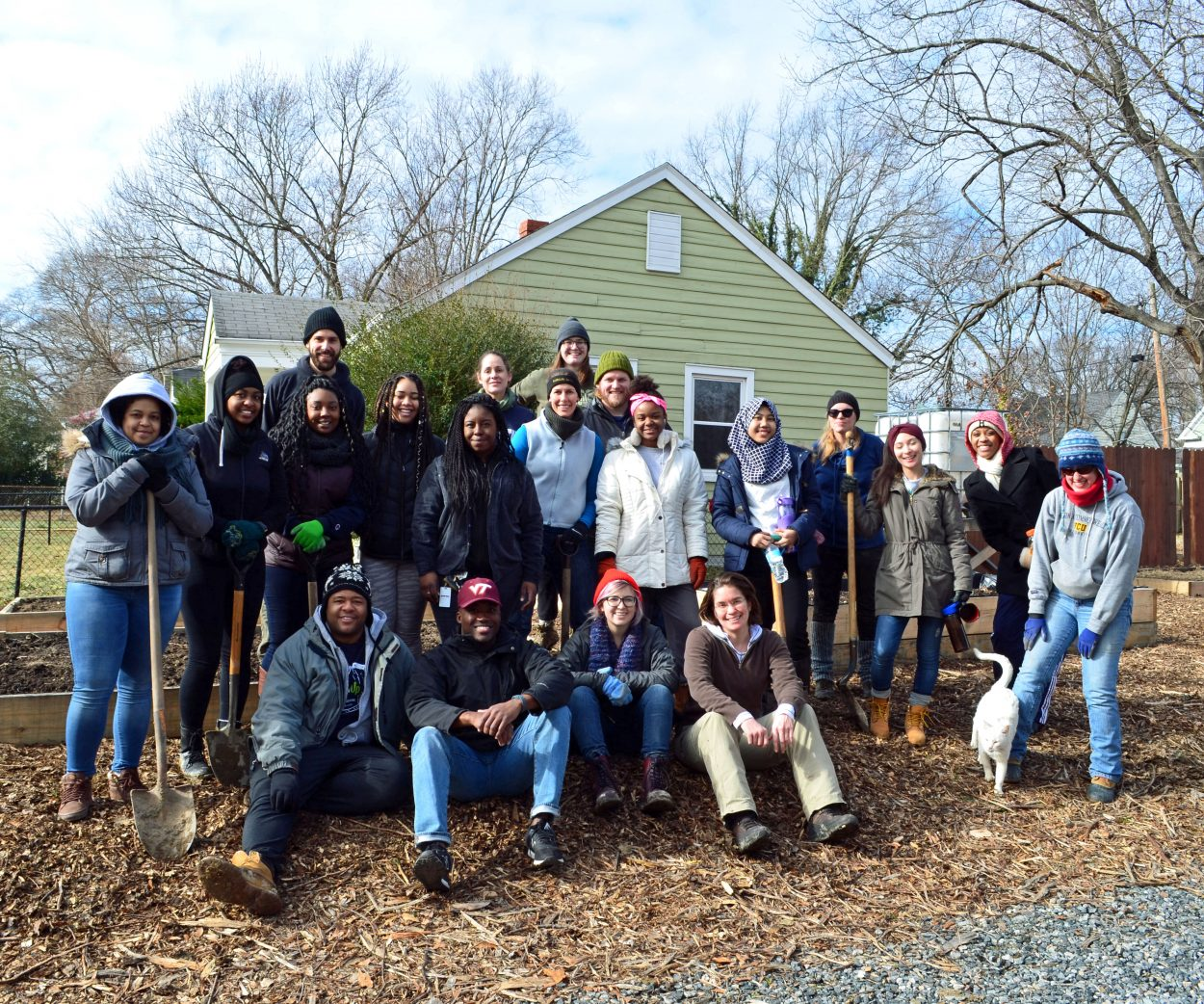 Group of volunteers poses together after building garden beds for an underserved neighborhood in urban Richmond