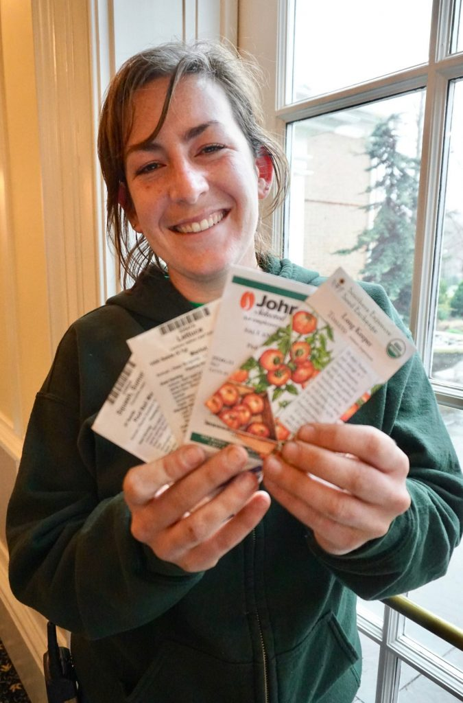 A horticulturists holds up packets of seeds
