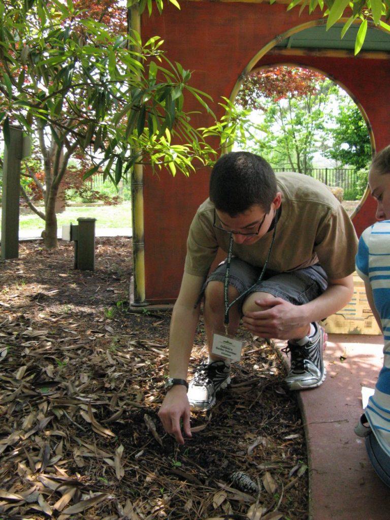 A young man weeding in the Children's Garden