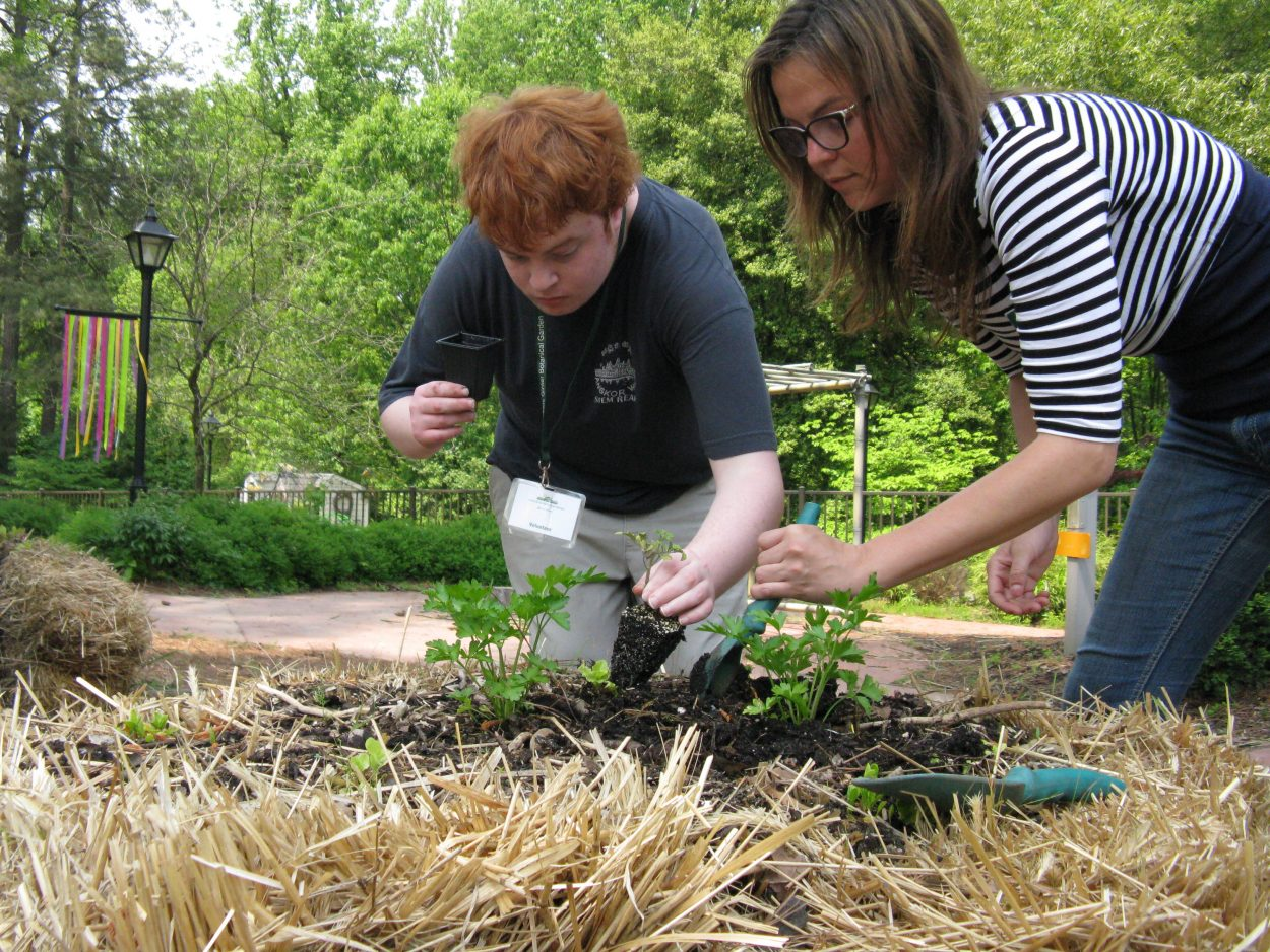 Young man gardening with the help of a teacher