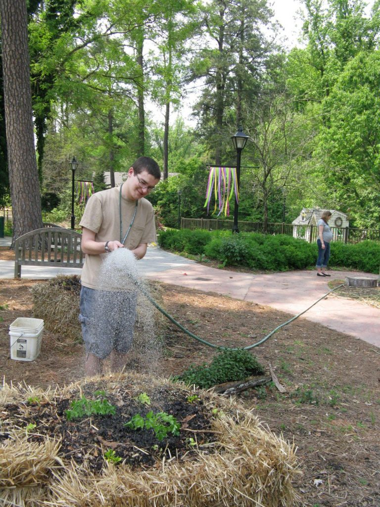 A youth with special needs working outside in the garden.