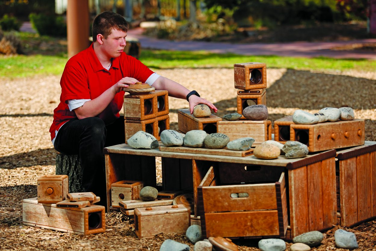 Tristin Compton rearranges objects in the Children's Garden as part of job skills training.