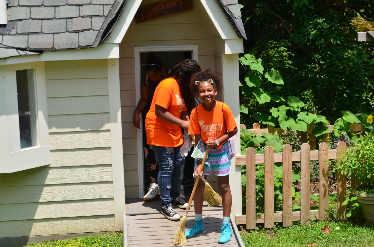 Smiling girl in an orange T-shirt standing on the ramp leading into the Garden Keeper's Cottage, sweeping it with a broom held between her feet.