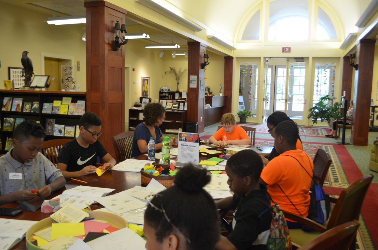 Image of several kids at a library table, all focused on origami instruction books. Several have pieces of colored paper in their hands and are in the process of folding.